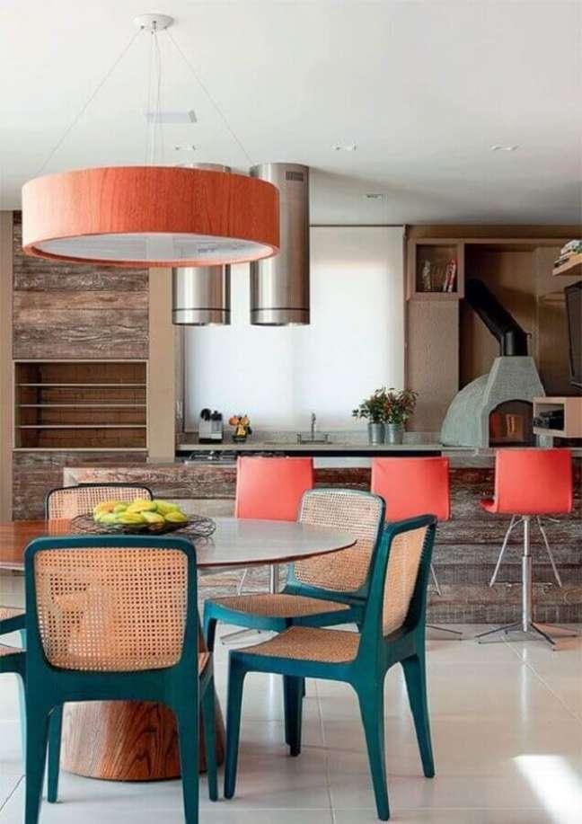 39. Lustre para área gourmet decorada com revestimento de madeira e cadeiras azuis – Foto: Pinterest