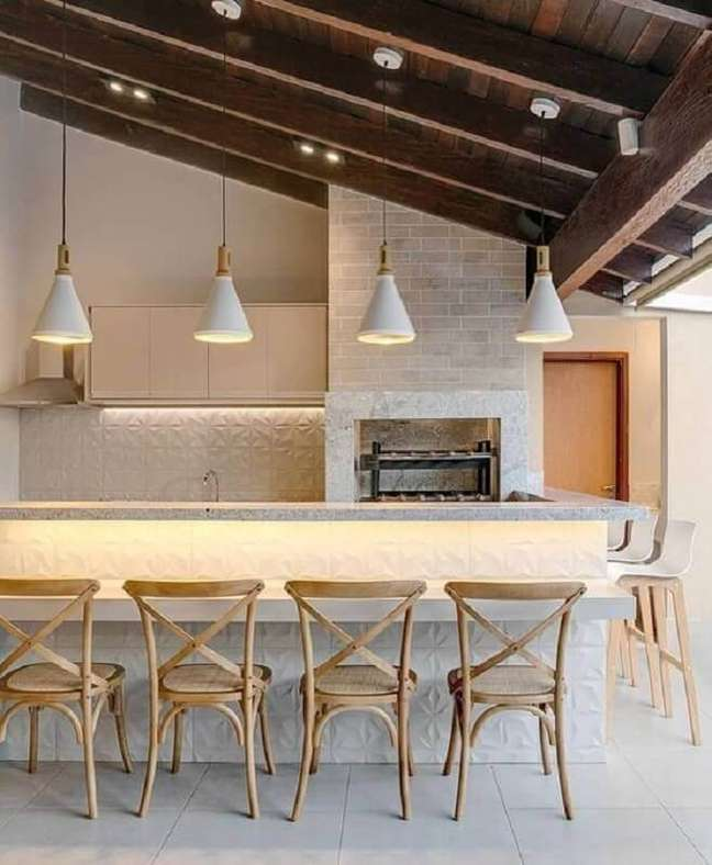 45. Lustre para área gourmet externa decorada com revestimento 3D e banquetas de madeira – Foto: Fashion Bubbles