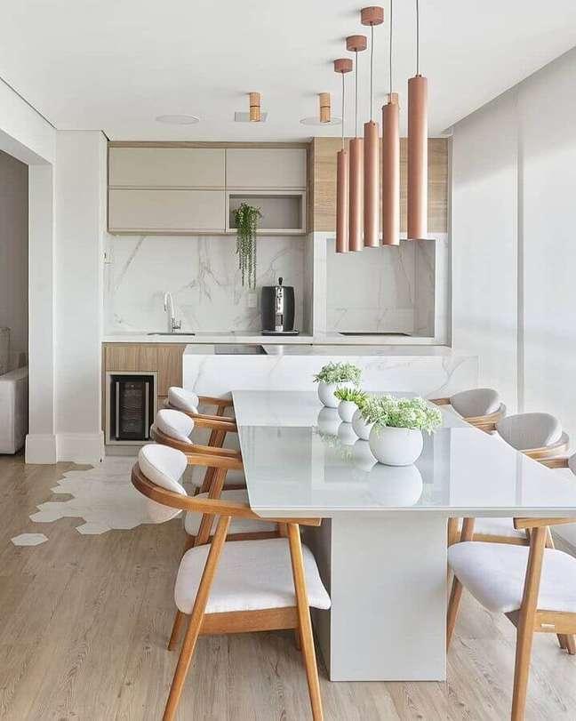 59. Lustre pendente para área gourmet moderna decorada com cadeiras de madeira para mesa branca – Foto: Decor Salteado