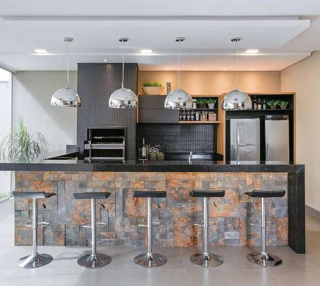 46. Lustre para área gourmet externa moderna decorada com revestimento preto para churrasqueira – Foto: Jeito de Casa