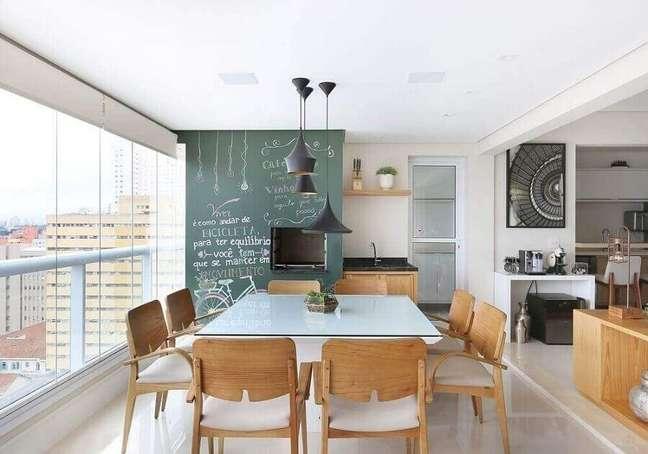 55. Lustre pendente para área gourmet decorada com mesa quadrada e parede de tinta lousa – Foto: Renata Cafaro