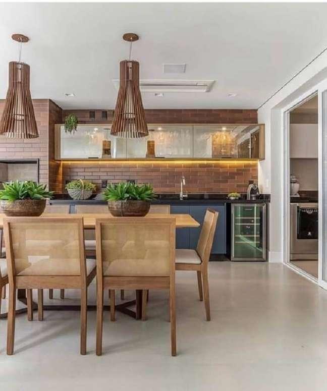 9. Lustre para área gourmet grande decorada com cadeiras de madeira e parede de tijolinho – Foto: Fashion Bubbles