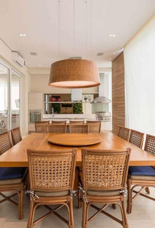 7. Lustre de madeira para área gourmet decorada com mesa quadrada e churrasqueira de vidro – Foto: Arkpad