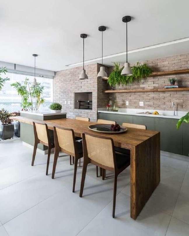37. Lustre para área gourmet decorada com mesa de madeira ligada à ilha – Foto: Jeito de Casa