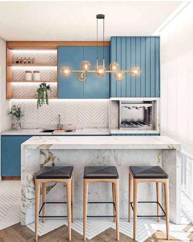 8. Decoração com lustre moderno para área gourmet planejada com bancada de mármore e armários azuis – Foto: Fashion Bubbles