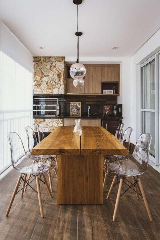 51. Lustre pendente para área gourmet de apartamento decorada com revestimento de pedra e mesa de madeira – Foto: Idealizzare Arquitetos