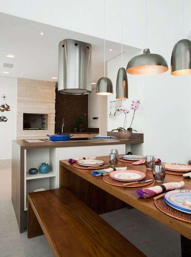 36. Lustre para área gourmet decorada com mesa de madeira e coifa redonda – Foto: Art Maison