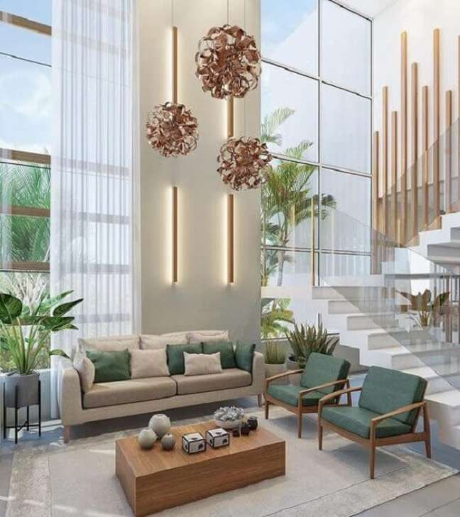 13. Sala de estar com decoração moderna e pé direito duplo. Projeto de Mayna Vaz Arquitetura