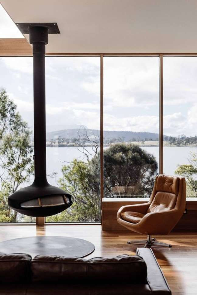 1. Lareira suspensa na sala de estar com poltrona de couro e móveis sofisticados – Foto ArchDaily