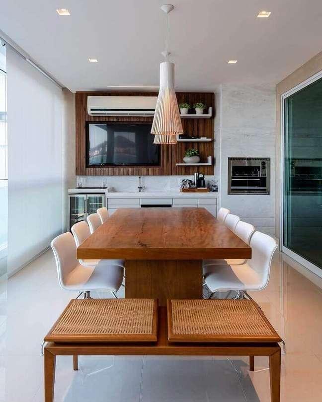 62. Mesa de madeira decorada com lustre para área gourmet planejada com churrasqueira – Foto: Dicas de Mulher