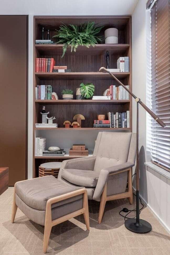 47. Poltrona confortável para leitura em sala decorada com estante de nichos – Foto: VOA Arquitetura