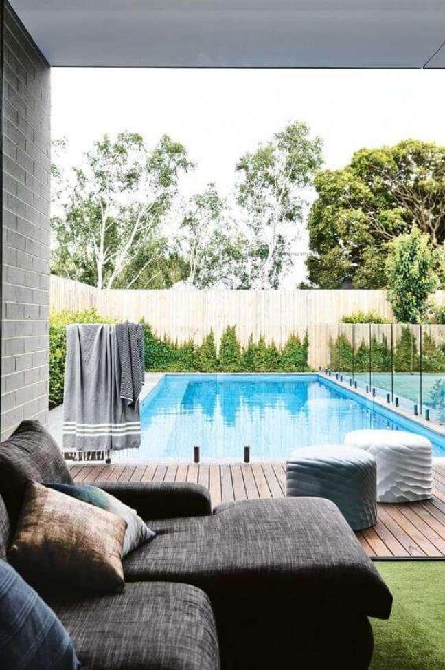 37. Área gourmet com sofá cinza confortável perto das piscinas modernas e deck de madeira – Foto Pinterest