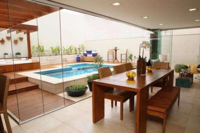 30. Piscinas modernas perto da varanda de vidro com móveis para receber amigos em casa – Foto Vanda Carvalho Barbosa