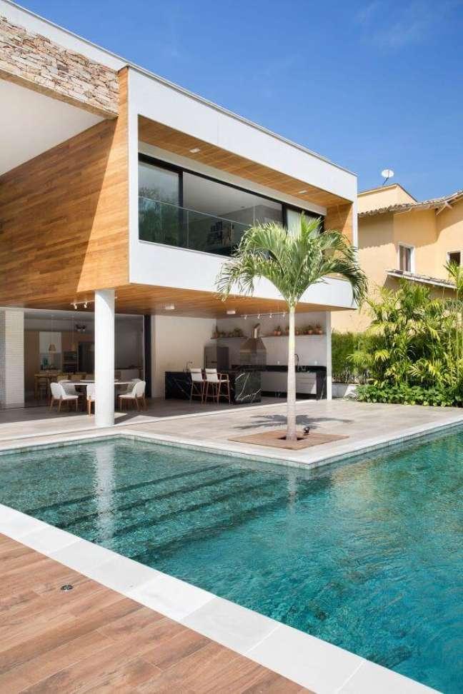 35. Área gourmet com piscinas modernas e estrutura de madeira – Foto Pinterest