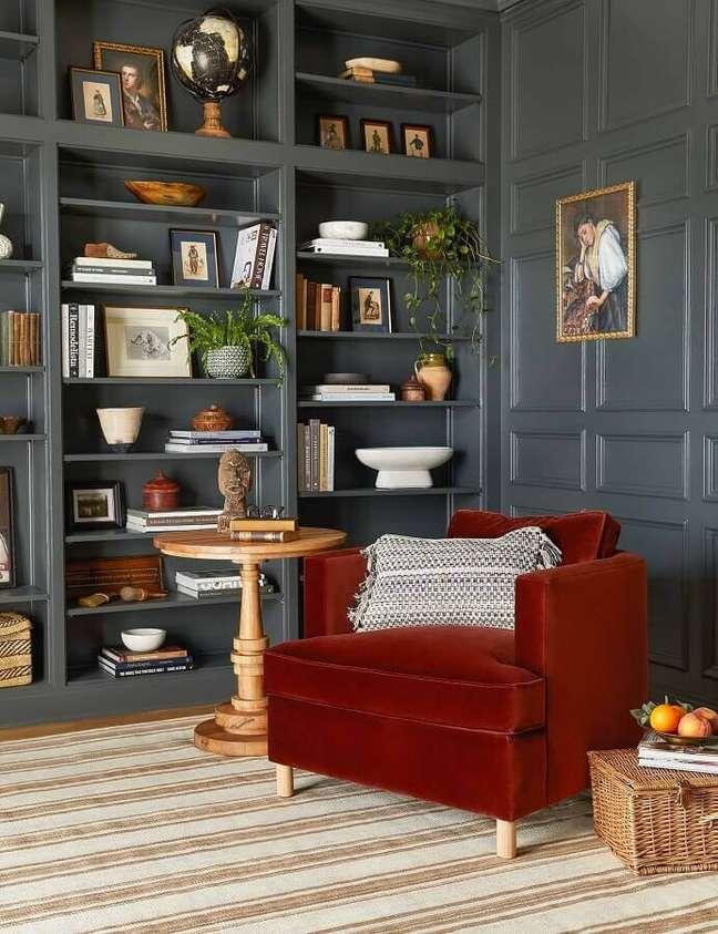 27. Decoração de sala com estante planejada cinza e poltrona confortável para leitura – Foto: Lulu & Georgia