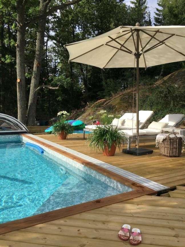 33. Área de piscina moderna com guarda sol para proteger a família dos raios uv – Foto Dream House cammy