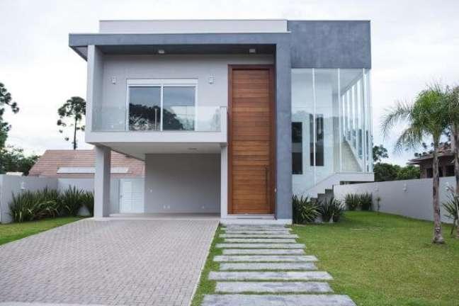 70. Ideia de cores para fachada de casas em tons de cinza e porta grande de madeira – Foto revistavd