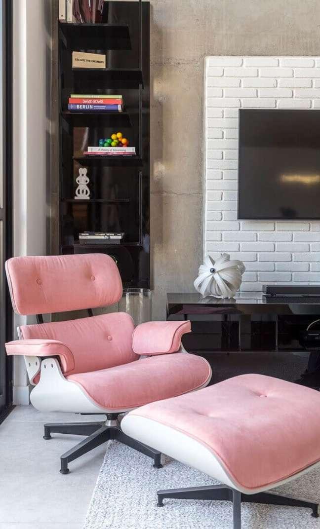 10. Decoração com parede de cimento queimado e poltrona confortável para sala de TV – Foto: Conexão Decor