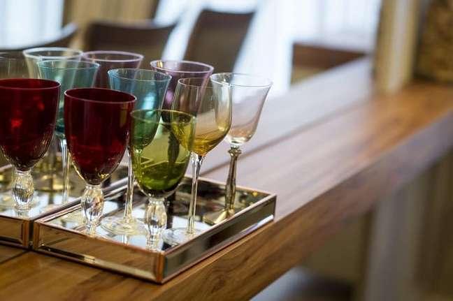 20. A bandeja para bar organiza taças coloridas no ambiente. Projeto de INOVA Arquitetura