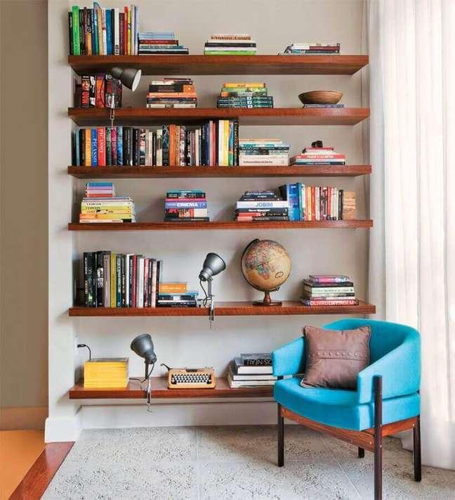 20. Decoração com prateleiras de madeira para livros e poltrona confortável para leitura – Foto: Jeito de Casa