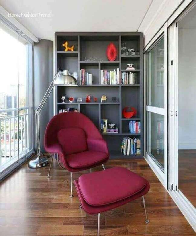 8. Cantinho de leitura na varanda decorada com estante cinza e poltrona confortável com puff – Foto: Home Fashion Trend