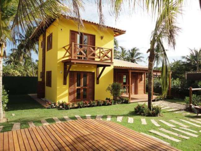 81. Casa com fachada amarela e janelas de madeira – Foto Pinterest