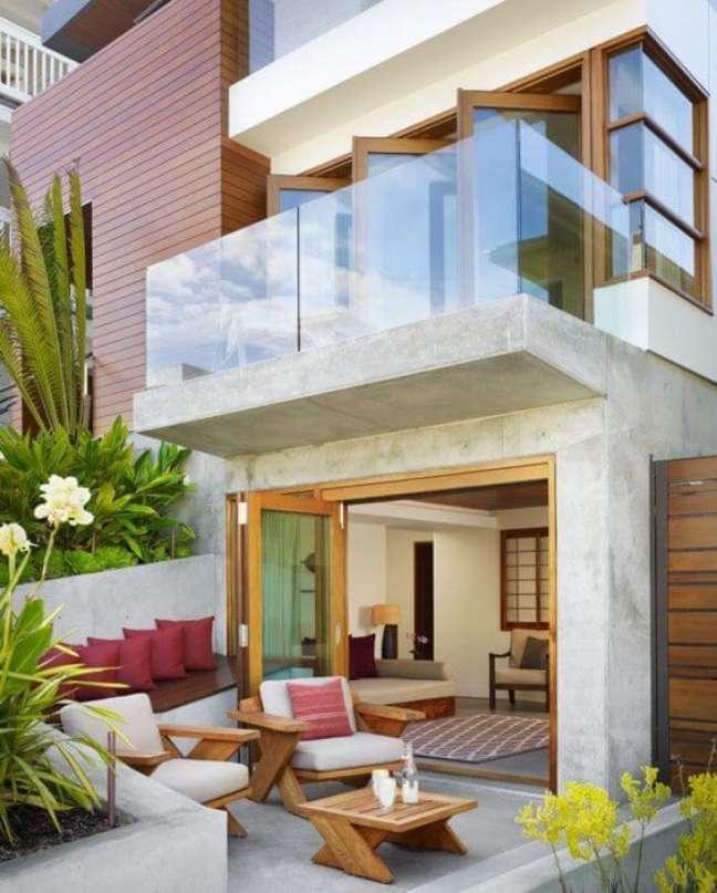 79. Revestimentos para fachadas de casas em cimento queimado com varanda de vidro e móveis confortáveis na área de lazer – Foto pinterest