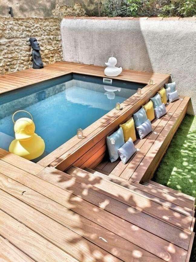 81. Piscinas modernas com deck de madeira e almofadas coloridas para deixar o ambiente mais confortável – Foto Pinterest