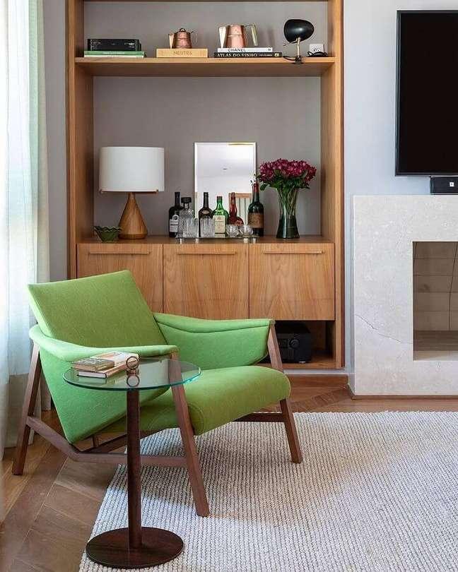 58. Poltrona confortável para sala de TV decorada com estante de madeira – Foto: Adriana Valle e Patrícia Carvalho