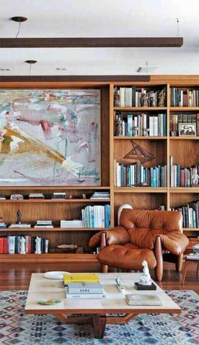 56. Poltrona confortável para sala de estar decorada com estante de madeira para livros – Foto: Pinterest