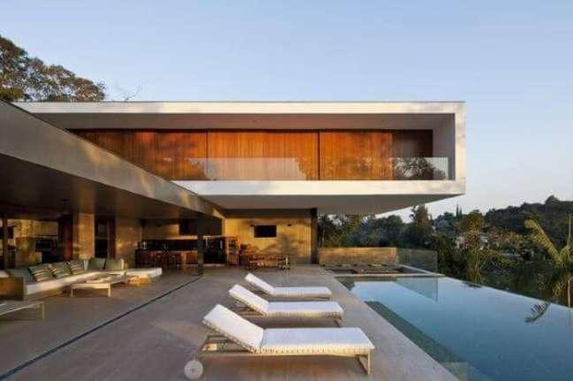 12. Móveis para piscina com espreguiçadeira branca e sofás na varanda – Foto Revista VD