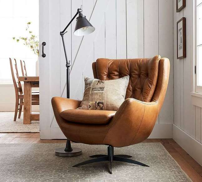 13. Cantinho de leitura decorado com poltrona confortável giratória e luminária de piso – Foto: Pottery Barn