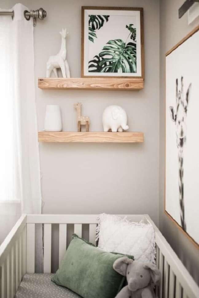 43. Prateleira de madeira e quadros decoram o quarto de bebê safari. Fonte: Pinterest