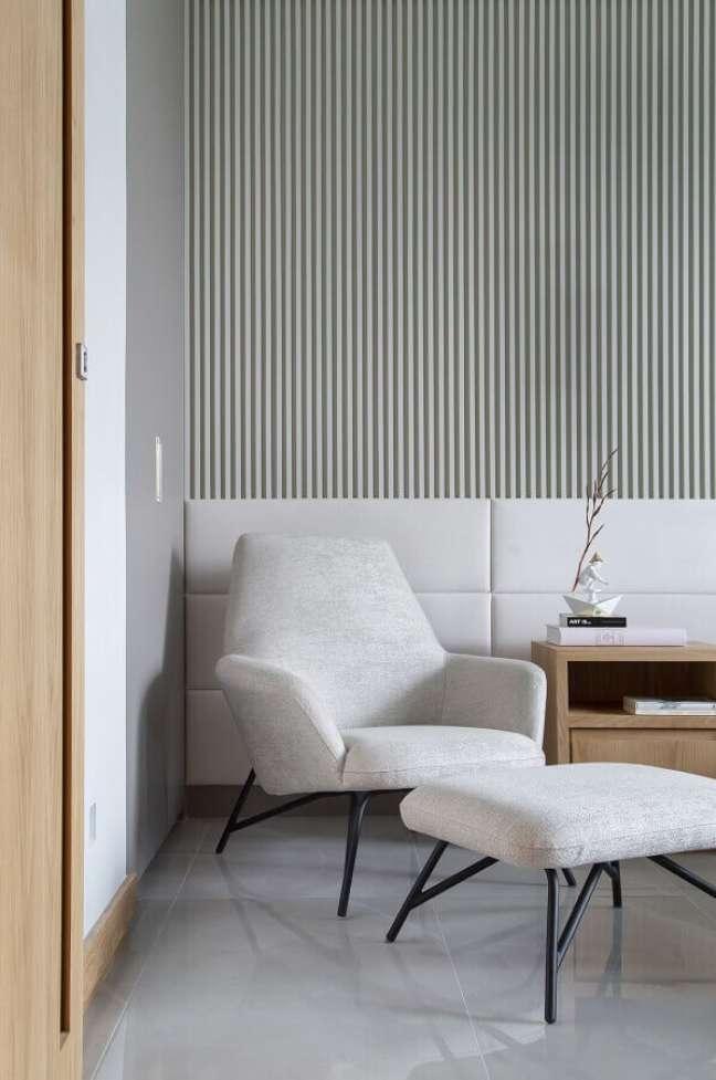 52. Poltrona confortável para quarto decorado com papel de parede listrado e cabeceira branca estofada – Foto: Casa de Valentina