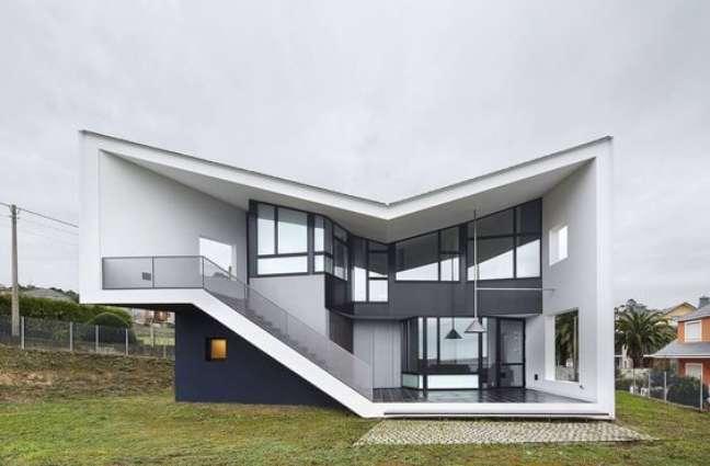 61. Fachadas de casas modernas na cor branca com detalhes em azul e janelas cinza escuro – Foto Arkpad