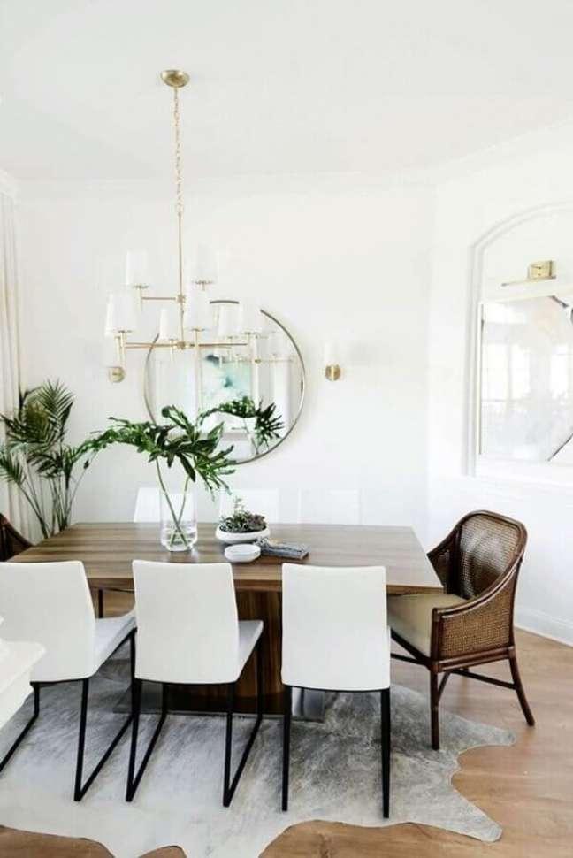 7. Poltrona confortável para sala de jantar branca decorada com espelho redondo – Foto: The Ever Girl