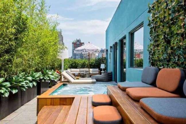 32. Área de lazer com guarda sol para piscinas modernas e cantinho planejado para descansar – Foto Pinterest