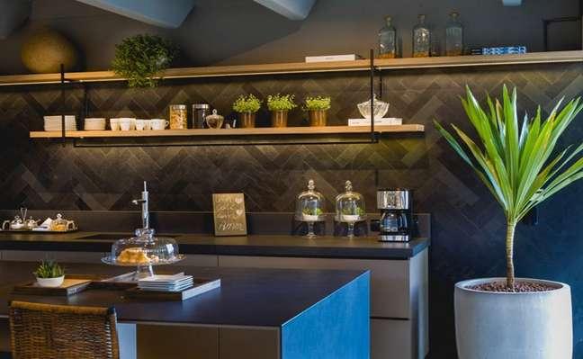 10. Cozinha com revestimento de ardosia preta e prateleiras de madeira para organizar o ambiente – Foto Mosarte