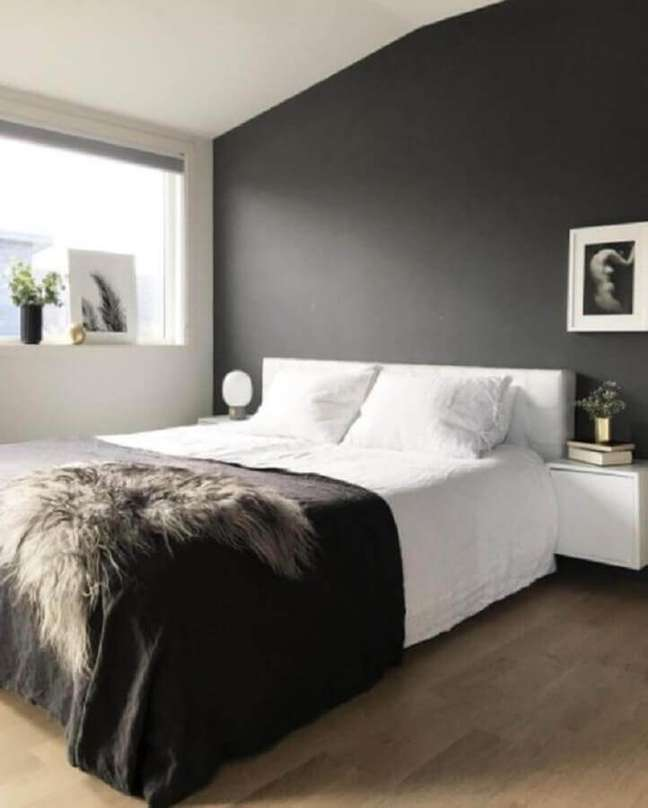 6. Decoração minimalista para quarto de casal preto e branco com lustre dourado – Foto: Home Bunch