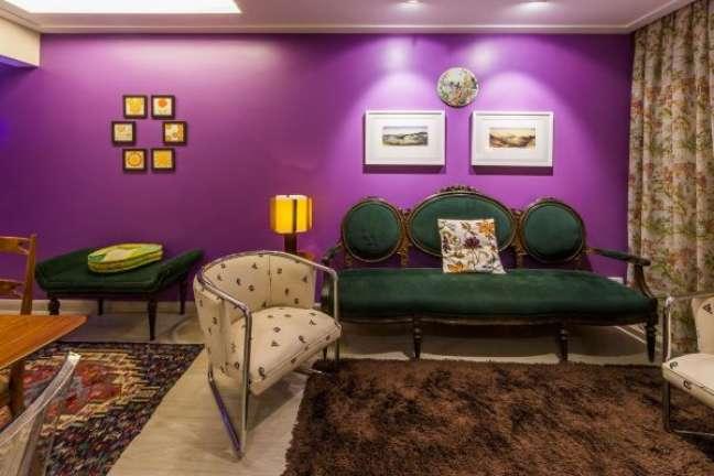 55. Sala com parede roxa e móveis vintage verde e madeira – Foto Enzo Sobocinski