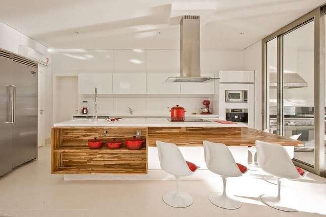 48. Decoração para cozinha aberta com ilha branca com bancada e nichos de madeira e cadeiras brancas – Foto: Marí Aní Oglouyan