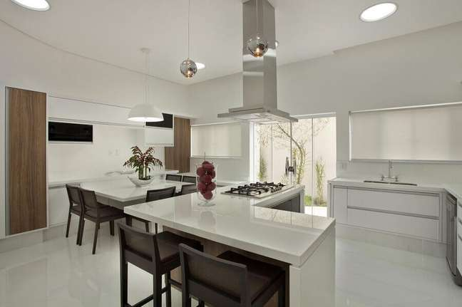 29. Decoração clean com balcão em L para cozinha aberta com sala de jantar – Foto: Aquiles Nicolas Kílaris