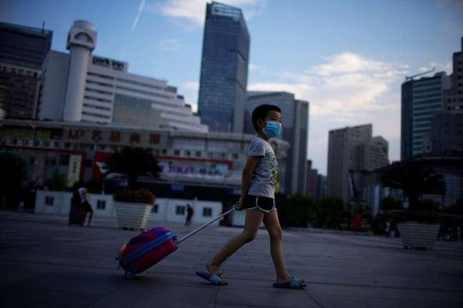 Menino de máscara protetora caminha perto da Estação Ferroviária de Xangai, cidade que registrou novos casos de coronavírus, China, 23 de agosto de 2021. REUTERS/Aly Song
