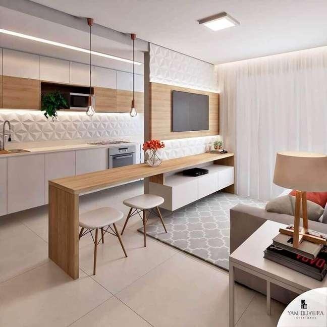 15. Bancada de madeira planejada para decoração de cozinha aberta com sala de TV – Foto: Yan Oliveira