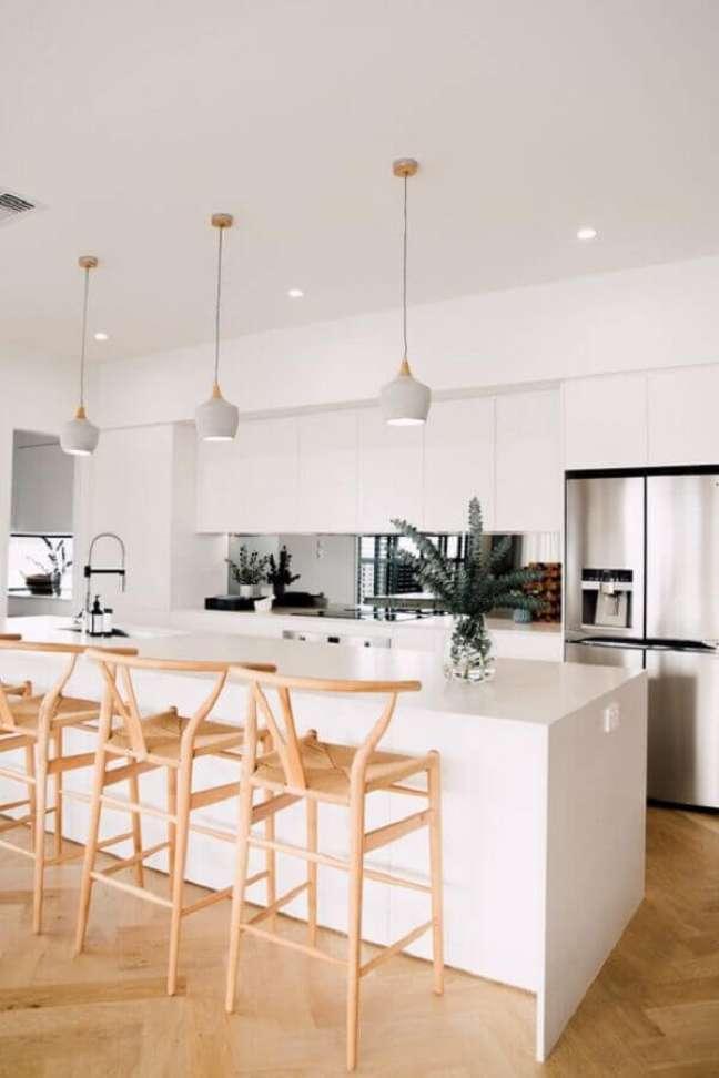17. Banqueta de madeira para decoração de cozinha aberta com ilha branca – Foto: Abidei Interiors