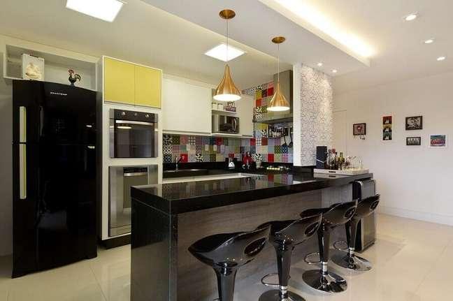 37. Decoração de cozinha aberta com revestimento colorido e banquetas pretas – Foto: Juliana Conforto