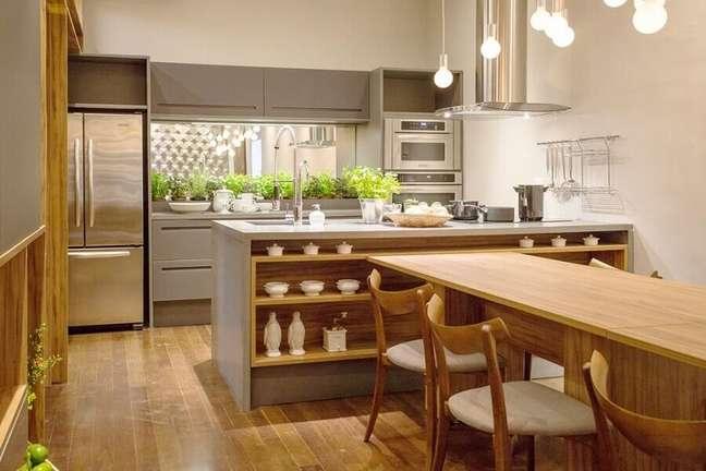 39. Decoração de cozinha aberta planejada com bancada de concreto com mesa de madeira integrada – Foto: Mary Oglouyan