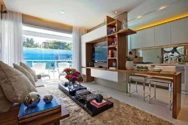 2. Cozinha aberta com sala de TV decorada com tapete bege felpudo – Foto: BOQ News
