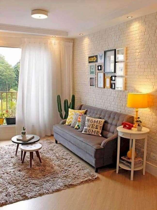 48. Sala de estar decorada com parede tijolinho branco e almofadas para sofá cinza – Foto: IO Home Decor