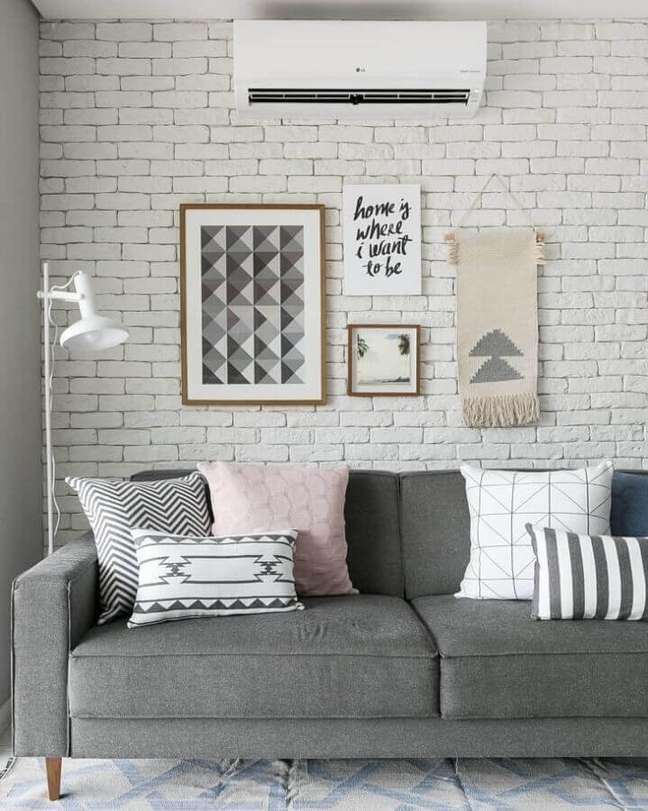 14. Combinação de almofadas para sofá cinza em sala decorada com parede tijolinho branco – Foto: Gisele Rampazzo